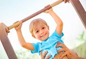 foto of daddy  - Closeup portrait of little happy boy lifting on crossbar - JPG