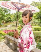 Asian woman in kimono holding an umbrella