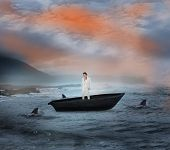 Composite image of thinking businesswoman in a sailboat being circled by sharks