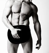 stock photo of six pack  - a muscular man posing artistic on white background - JPG