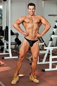 stock photo of lats  - young bodybuilder in the gym posing front lat spread - JPG