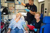 picture of stretcher  - Confident paramedic treating injured elderly patient on stretcher in ambulance - JPG
