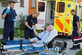 stock photo of stretcher  - Emergency team examining injured senior patient lying on stretcher outdoors - JPG