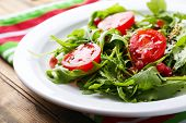 Green salad made with  arugula, tomatoes and sesame  on plate, on wooden background