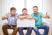 friendship and advertising concept - smiling male friends holding white blank board and showing thumbs up