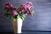 Beautiful lilac flowers in vase, on color wooden background