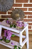 Beautiful lilac flowers in vases, on wooden ladder, on color wall background