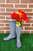 Composition of colorful tulips in rain boots on bright background
