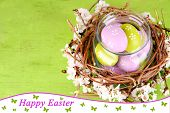 Composition with Easter eggs and blooming branches in glass jar and decorative nest, on  color wooden background