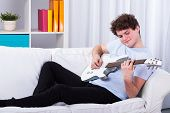 Man Lying On A Couch And Playing Guitar