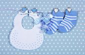 Baby Boy Nursery Blue Socks And Bib, With Dummy Pacifier Hanging From Pegs On A Line
