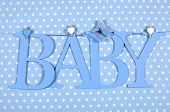 foto of teething baby  - Baby boy nursery blue BABY letters bunting hanging from pegs on a line against a blue polka dot background for baby shower or newborn greeting card - JPG