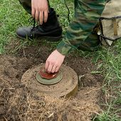 stock photo of landmines  - Minesweeper neutralizes mine - JPG