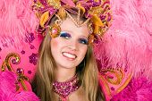Portrait of young woman in pink carnival costume, close up