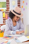 Smiling female interior designer using laptop at office desk