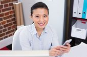 Portrait of smiling female executive text messaging in the office