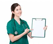 Woman doctor with finger point to blank page on clipboard