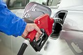 Man Pumping Gasoline With Red Handle