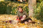 woman and little girl in autumn park with apple basket