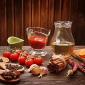 everything on wood table for cooking (tomato garlic spices olive oil)
