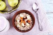 Bowl of oatmeal, dried apricots, apples and yogurt on napkin on blue wooden background