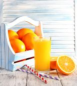 Glass of orange juice and fresh oranges in wooden box on wooden table on wooden wall background