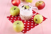 Oatmeal with yogurt in pitcher and apples on napkin on wooden background