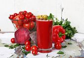 Glass of tomato juice and fresh vegetables on old wooden table on wall background
