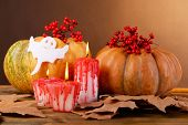 Composition of  pumpkin, candle and Halloween decorations on wooden table, on dark color background