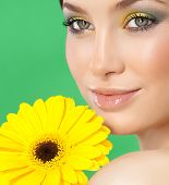 closeup portrait of attractive  caucasian smiling woman brunette isolated on white studio shot lips face closeup skin makeup eyes  head and shoulders looking at camera yellow flower