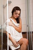 stock photo of shower-cubicle  - Young woman wiping body by a towel after a shower - JPG