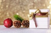 Gift box and Christmas decor on table on shiny background