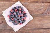 Iced berries on plate, on wooden background