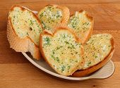 Slices of garlic & herb bread in a ceramic serving dish.
