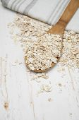 stock photo of oats  - Whole grain rolled oats with wooden spoon and napkin - JPG