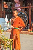 CHIANG MAI, THAILAND - APRIL 14, 2011: Boy in orange clothes of Buddhist monk from hose watering the flowers