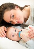 cute mother at home feeding baby son with a milk bottle