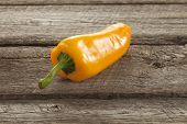Yellow Sweet Pepper On A Rough Wood Surface