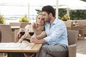 Loving young couple having red wine at outdoor restaurant