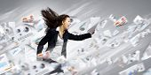 stock photo of late 20s  - Young determined businesswoman walking against strong wind - JPG