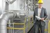 Portrait of young male architect holding blueprint by machinery at industry