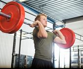 Fit young man lifting barbell at gym