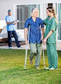 Female nurse helping senior woman to use crutches with caretaker in background at nursing home lawn
