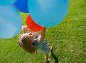 High angle view of mother and daughter holding colorful helium balloons in park