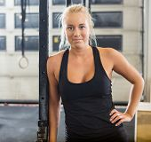Portrait of confident fit woman standing with hand on hip at healthclub