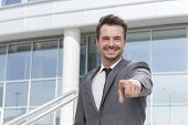 Portrait of smiling businessman pointing at you outside office building