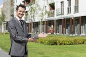 Portrait of happy real estate agent presenting office building