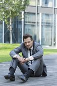 Full length portrait of stressed businessman sitting on path outside office
