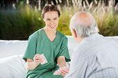 Smiling female nurse playing cards with senior man at nursing home