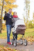 parenthood, gesture, family, season and people concept - smiling couple with baby pram waving hands in autumn park